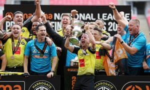 Josh Falkingham of Harrogate Town lifts the trophy after his team's comfortable victory in the National League play-off final against Notts County.