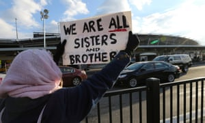 A woman holds a sign outside JFK airport in New York during a protest against Donald Trump's executive order banning entry of citizens from seven Muslim-majority countries.