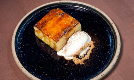 A square of bread and butter pudding with a caramelised top and a scoop of ice-cream next to it on a round dark blue plate