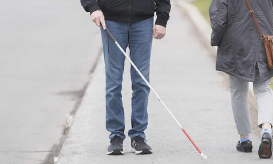 A visually impaired man uses a white cane