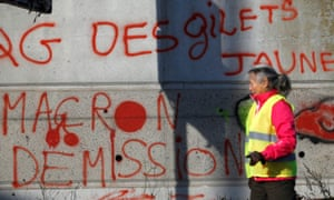 A protester outside a shopping centre in Nantes, walks past a wall with graffiti saying: 'Macron, resign.'
