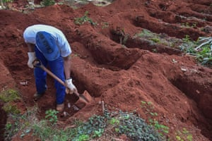 An employee digs a grave at Vila Formosa, where authorities say they have already seen 30% increase in the number of burials