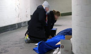 Outreach workers from St Mungo's homeless charity talking to a homeless person in London.