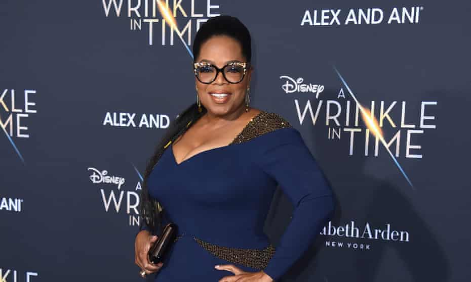 Oprah in a blue dress standing with her hands on her hips in front of a blue background, as though being pohtographed on a red carpet