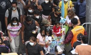مشاة يرتدون أقنعة الوجه أثناء السير في سوق ميسا ريدوندا ، وهو مكان شهير للتسوق في عيد الميلاد في ليما ، بيرو.