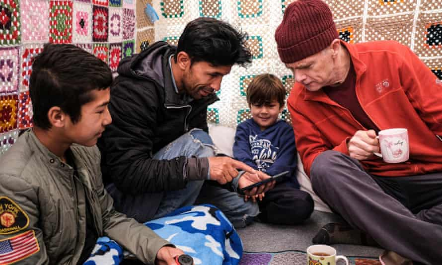 Abdullah Najafi (second left), from Afghanistan, and two of his children – Mohammad (left), 14, and Meraj, five – show photos and share tea with Sam Wollaston inside their tent at Moria