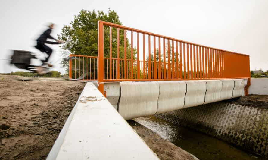 A cyclist crosses the 3D-printed concrete bike bridge in Gemert.