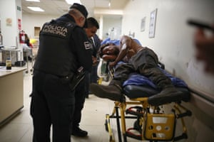 Police interrogate officers one of four men injured in a drive-by shooting at a Tijuana petrol station on 8 October.