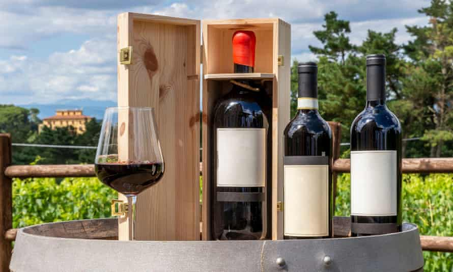 Three bottles including a magnum in the wooden box and a glass of red wine on a wooden barrel