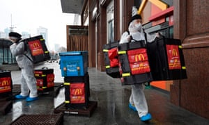 McDonalds workers wear protective suits as a preventive measure against the Covid-19 coronavirus as they prepare to deliver food to residents in Wuhan, in China's central Hubei province on February 26, 2020.