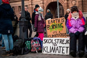 Swedish climate activist Greta Thunberg (centre) protests in front of Swedish parliament, with a placard depicting a burning map of Australia.