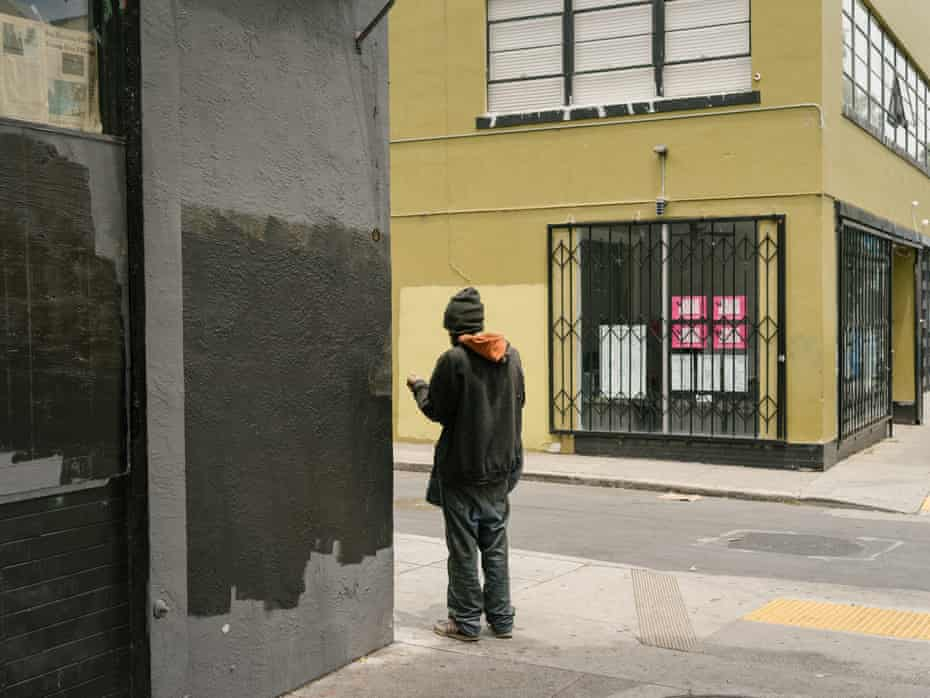 A homeless man picked up a syringe along Mission Street in downtown San Francisco.