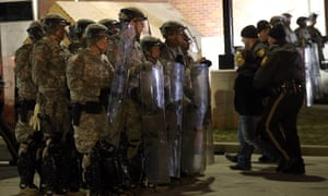 Police officers escort an arrested protestor who was blocking the street in front of the Ferguson police station past members of the National Guard in Ferguson, Missouri