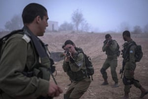 A female soldier takes aim as Israeli combat soldiers of the mixed-gender Bardales battalion take part in a long day of practise in heavy fog in Nitzana, Israel