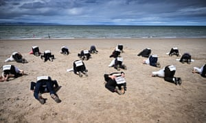 An Extinction Rebellion heads-in-the-sand protest in Nairn, Scotland, earlier this month. Campaigners held the event to draw attention to a meeting of the G20 countries, which XR believe must could do more to tackle climate change.