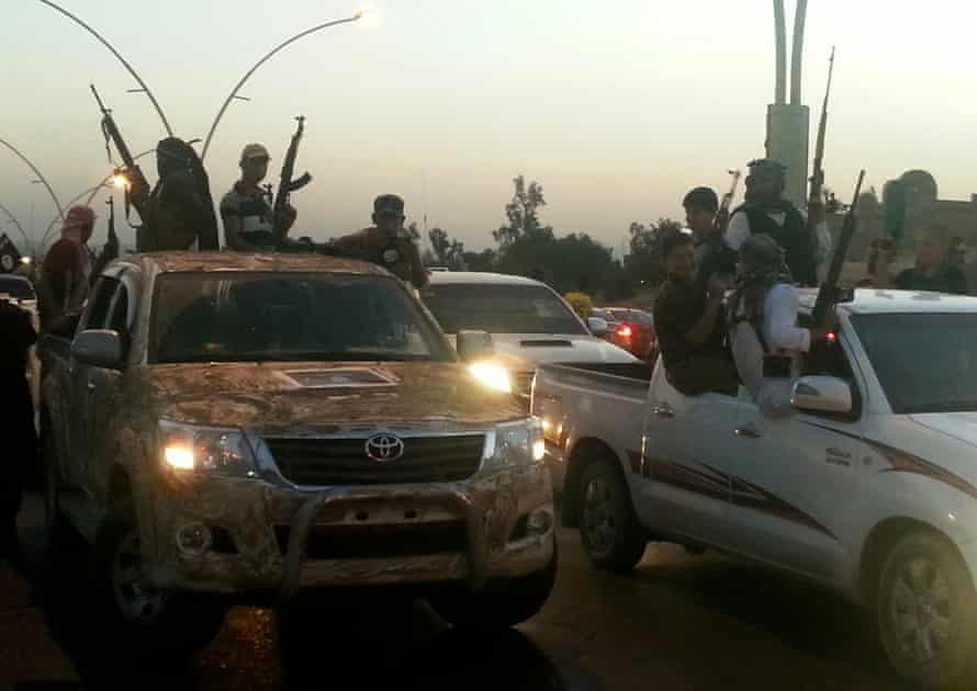Isis fighters celebrate while sitting on vehicles in the city of Mosul, 23 June 2014.