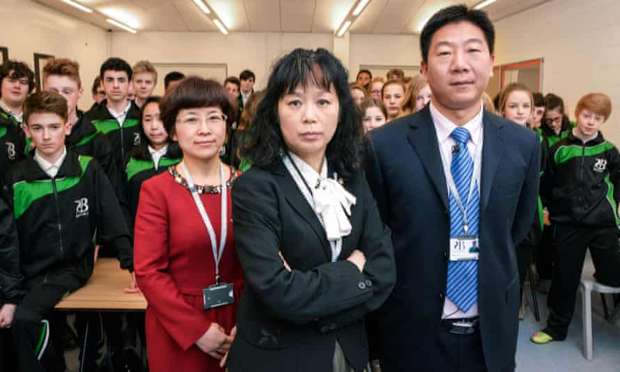 Shot from the BBC's TV programme Are Our Kids Tough Enough? Chinese School showing three teachers (left to right Li Aiyun, Jun Yang-Williams, Hailian Zou) standing in front of a classroom of pupils