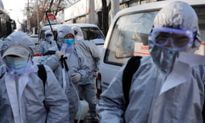 Workers in protective suits after disinfecting a residential area in Beijing, China, to control the spread of coronavirus