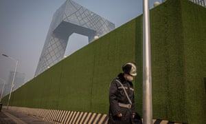 A worker wearing a protective face mask walks next to a construction site in Beijing.