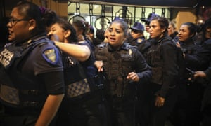 Police watch the second floor of their station burn, set on fire by protesters during a demonstration sparked by a string of alleged sexual attacks by police officers in Mexico City