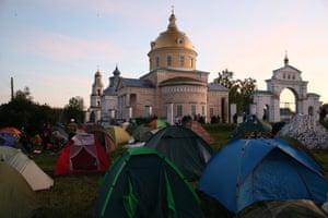 Pilgrims set up tents by the St Nicholas Church in the village of Velikoretskoye
