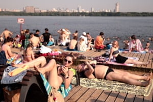 People sunbathe on a beach in Strogino district in north-western Moscow