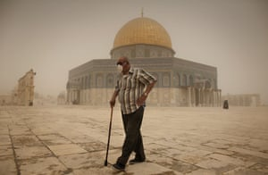 A Palestinian man wears a mask to protect his face from the dust as he walks past the Dome of the Rock Muslim shrine in the al-Aqsa mosque compound in the old city of Jerusalem