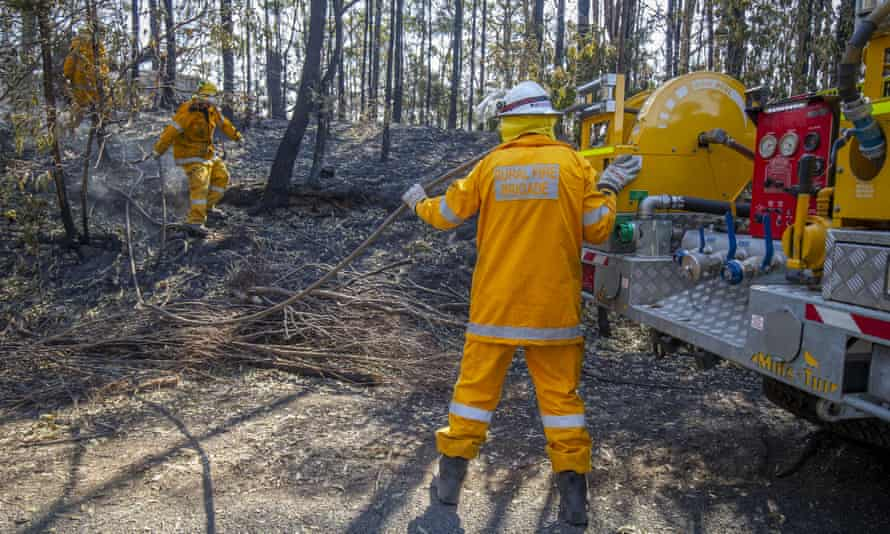 Queensland firefighters put out spot fires on Binna Burra Road on 12 September.