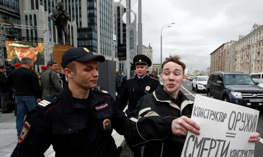 A man is detained by police as he holds a sign reading, 'a creator of weapons is a creator of death'.