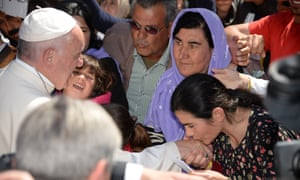 A woman kisses the hand of Pope Francis as he greets people at the Moria refugee camp.