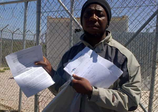 Samuel Aneke from Nigeria shows his medical papers outside the Chios detention camp.
