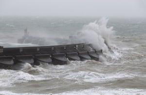Waves crash over the marina wall in Brighton