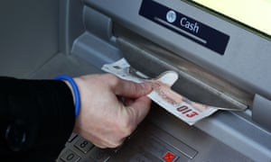 A person withdraws notes from a cash machine