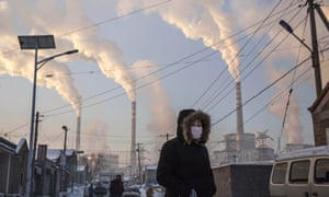 A woman walks past a coal-fired power plant in Shanxi, China.