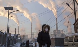 A Chinese woman wears a mask while walking in a neighbourhood next to a coal-fired power plant in Shanxi, China.