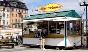Customer at the snack bar with sale of freshly fried herring at Sodermalmstorg in Stockholm.MJDMP6 Stockholm, Sweden - July 10, 2016: Customer at the snack bar with sale of freshly fried herring at Sodermalmstorg in Stockholm.