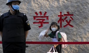A student wearing a face mask to help curb the spread of the coronavirus waves next to a masked security guard as she arrives to a primary school in Beijing, Monday, 7 September 2020.