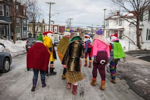 """A group goes mummering on the streets of St John's, Newfoundland. Participants are advised on the parade's website: """"Foolish is the new normal, underwear is outwear, and a curtain is more than just a curtain. So shake out those long johns and borrow your Aunt's size 42 bra!"""""""
