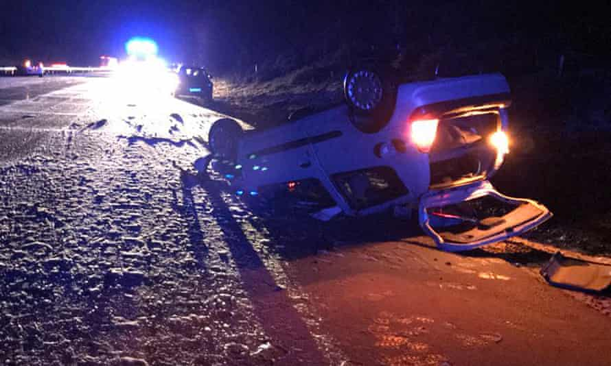 An overturned car on the M20 with snow on the ground