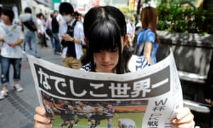 A Japanese young woman reads an edition of the Asahi newspaper