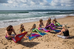 Mermaiding instructor Michelle Forsbrey, speaks with students of her Mayim Mermaid academy during a lesson on Boscombe beach, Bournemouth, England, UK