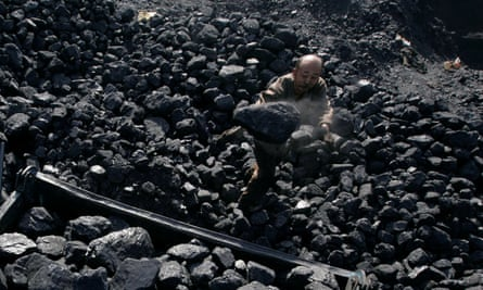 A man loads coal on to a cart in Shaanxi province, where 19 miners have after a coalmine collapse.