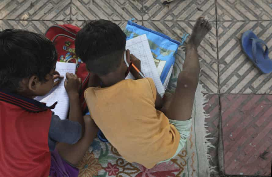 Children practice writing numbers during a class taught three times a week on the street in Delhi, India.