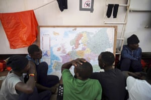 Rescued migrants look at a map of Europe onboard the Ocean Viking ship as it sails in the Mediterranean