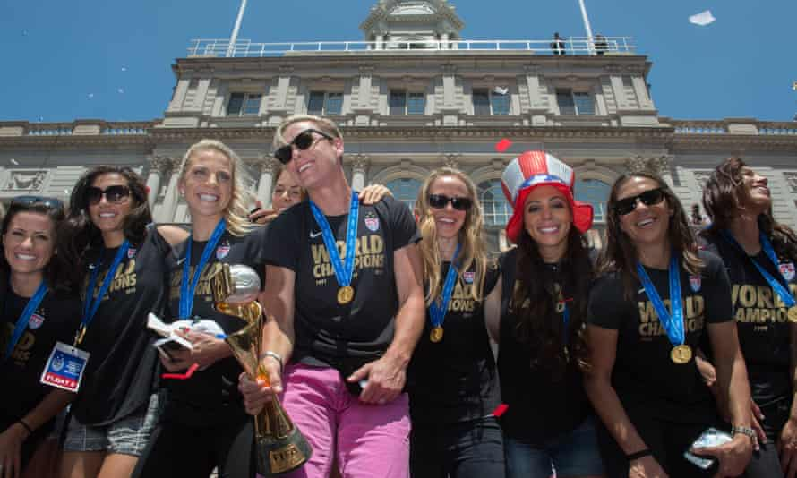 Flanked by her teammates, Abby Wambach holds their trophy at New York's city hall as the US Women's World Cup soccer champions celebrate following a ticker-tape parade.