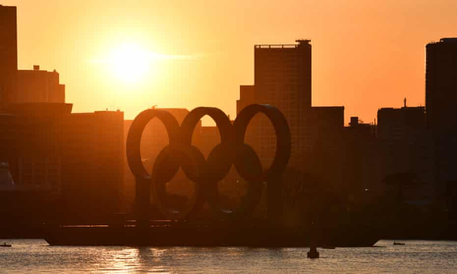 The sun sets behind the Olympic rings
