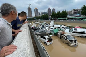 Zhengzhou, China. People look at cars sitting in floodwaters after heavy rains hit the city in China's central Henan province