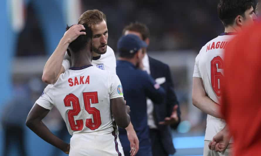 England's Harry Kane, centre, consoles Bukayo Saka after his missed penalty