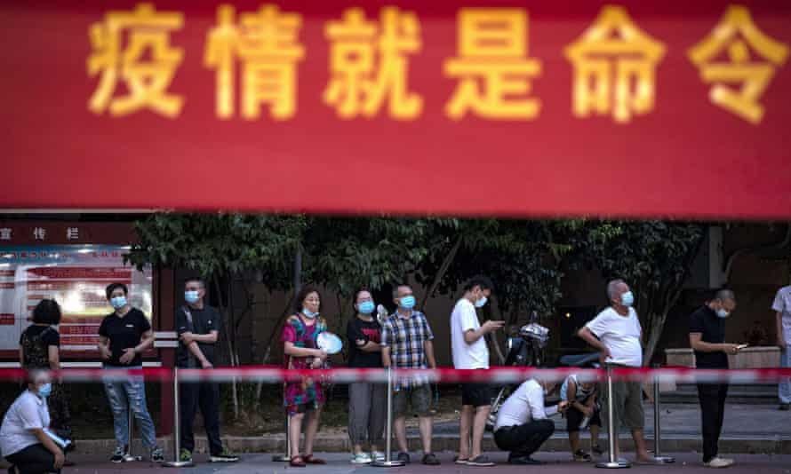Residents line up for Covid-19 tests near a banner with the words 'Epidemic is order' in Wuhan, central China's Hubei Province