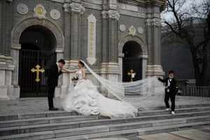 A couple pose for wedding photos outside a church in Beijing, China